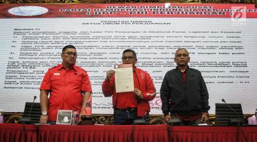 Sekjen DPP PDIP Hasto Kristiyanto (tengah) menunjukkan surat perintah Ketua Umum PDIP Megawati Soekarnoputri saat jumpa pers di Kantor DPP PDIP, Jakarta, Selasa (16/4). Megawati memberi lima perintah kepada kader dan jajarannya jelang pemungutan suara Pemilu 2019. (Liputan6.com/Faizal Fanani)