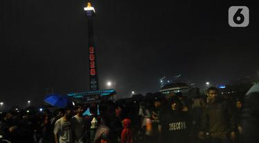 Pengunjung memadati kawasan Monumen Nasional saat malam pergantian tahun, Jakarta, Rabu (1/1/2020). Penampilan video mapping mewarnai kemeriahan malam pergantian tahun baru di kawasan Monumen Nasional, Jakarta. (Liputan6.com/Helmi Fithriansyah)
