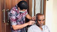 Bagi CEO Persik Abdul Hakim Bafagih pandemi COVID-19 bisa merekatkan hubungan keluarga. Itu nampak ketika Hakim Bafagih mencukur rambut sang ayah, Abdul Bagi di teras rumahnya. (Bola.com/Gatot Susetyo)