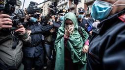 Petugas bantuan Italia bernama Silvia Romano yang dibebaskan oleh militan Somalia, dikawal polisi Italia (Carabinieri), tiba di rumahnya di Milan, 11 Mei 2020. Silvia, 25 tahun, mengakui alasan dia memeluk Islam bukan karena pernikahan atau menjalin hubungan dengan pria mana pun. (AP/Luca Bruno)