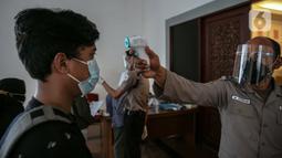Petugas mengecek suhu tubuh pekerja yang akan mengikuti vaksinasi COVID-19 di Gedung Kemenaker, Jakarta, Selasa (4/5/2021). Untuk memperingati Hari Buruh Internasional atau May Day, pemerintah melakukan vaksinasi bagi 1.000 pekerja. (Liputan6.com/Faizal Fanani)