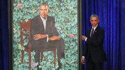 Presiden AS ke-44 Barack Obama menujuk lukisan dirinya saat upacara peresmian di Galeri Potret Nasional Smithsonian, Washington DC (12/2). Potret Presiden Obama ini dibuat oleh Kehinde Wiley. (Mark Wilson/Getty Images/AFP)