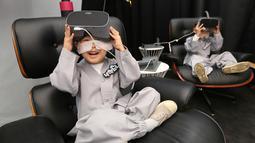 Dua anak lelaki bersiap menggunakan perangkat Virtual Reality (VR) sebelum mencoba layanan 5G di tempat pengalaman LG UPlus 5G di Seoul, Korea Selatan (7/5/ 2019). Perayaan ulang tahun Buddha akan jatuh pada 12 Mei mendatang. (AP Photo/Ahn Young-joon)
