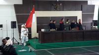 Bahar bin Smith mencium bendera merah putih usai menjalani sidang vonis di Pengadilan Negeri Bandung, Selasa (9/7/2019). (Liputan6.com/Huyogo Simbolon)