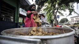 Pedagang saat memasak ketupat yang akan dijual di pinggir jalan kawasan Rawamangun, Jakarta, Senin (19/7/2021). Pedagang membanderol ketupat siap santap tersebut mulai dari harga Rp30 ribu hingga Rp40 ribu per ikat (10 buah) tergantung besar kecil ukuran. (merdeka.com/Iqbal S. Nugroho)