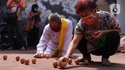 Warga keturunan Tionghoa mencoba mendirikan telur saat perayaan Peh Cun di Khongcu Bio Litang di Pasar Lama, Kota Tangerang, Kamis (25/6/2020). Prosesi yang digelar setiap tanggal 5 bulan 5 penanggalan Tionghoa itu menjadi ungkapan syukur atas segala rezeki dari Tuhan. (Liputan6.com/Angga Yuniar)