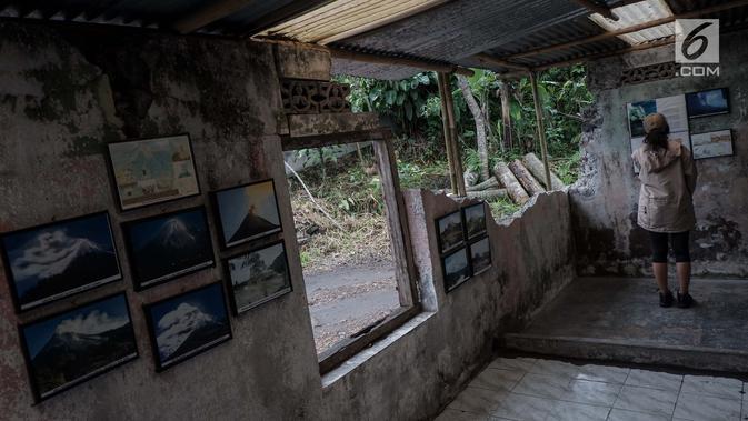 Pengunjung melihat foto dahsyatnya erupsi Gunung Merapi tahun 2010 di Galeri Sarsuadji, Sleman, Minggu (26/11). Di gaeleri ini terpajang sejumlah foto yang menggambarkan suasana saat peristiwa letusan Merapi pada 2010 lalu. (Liputan6.com/Faizal Fanani)