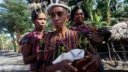 Sejumlah wanita memainkan alat musik tradisional dalam upacara peresmian bantuan bedah rumah di Desa Oebelo, NTT, Selasa (14/8). Upacara penyambutan diwarnai dengan tarian-tarian menggunakan alat musik baba khas daerah itu. (Liputan6.com/Johan Tallo)
