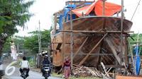 Warga melintas di area pembuatan perahu di Balongan, Indramayu, Jawa Barat, Jumat (15/1/2016). Dibutuhkan waktu selama delapan bulan untuk menyelesaikan satu unit perahu yang dijual seharga Rp.4 miliar - Rp.5 miliar tersebut. (Liputan6.com/Helmi Afandi)