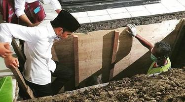Presiden Joko Widodo atau Jokowi saat turun ke liang lahat untuk memakamkan jenazah ibundanya Sudjiatmi Notomihardjo di pemakaman keluarga di Mundu, Kabupaten Karanganyar, Jawa Tengah, Kamis (26/3/2020). Sujiatmi Notomiharjo wafat pada Rabu 25 Maret 2020 pukul 16.45 WIB. (dok.istimewa)