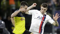 Bek Dortmund, Raphael Guerreiro berebut bola dengan bek PSG, Thomas Meunier pada pertandingan leg pertama babak 16 Liga Champions di Dortmund, Jerman (18/2/2020). Dortmund menang 2-0 atas PSG. (AP Photo/Michael Probst)