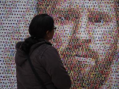 Seorang wanita memandangi mural Lionel Messi di Casa Rosada Museum, Buenos Aires, Argentina, Rabu (20/6). Mural terbuat dari dua ribu stiker figur pemain Argentina dalam Piala Dunia sepanjang masa. (Eitan ABRAMOVICH/AFP)