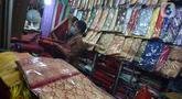 Aktivitas jual beli kain ulos di pasar proyek Senen, Jakarta, Kamis (21/10/2021). Sejak status PPKM turun dari level 3 menjadi level 2, pengunjung ramai mendatangi toko membeli kain ulos untuk upacara pernikahan adat dengan kisaran harga dari Rp. 500.000 hingga jutaan rupiah. (merdeka.com/Imam Buhor