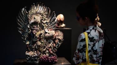 """Seorang pengunjung sedang melihat patung yang berjudul """"Two Garudas"""" karya seniman Inggris, Damien Hirst saat pameran di Venice, Italia (6/4). Karya patung tersebut terbuat dari logam yang dibalut dengan terumbu karang. (AFP Photo/Miguel Medina)"""