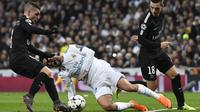 Pemain Real Madrid, Isco (tengah) jatuh saat berebut bola dengan pemain PSG, Marco Verratti (kiri) pada laga 16 besar Liga Champions di  Santiago Bernabeu stadium, Madrid, (14/2/2018).  Madrid menang 3-1. (AFP/Christophe Simon)