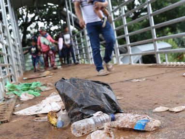 Kemasan botol air mineral berceceran di koridor Jembatan Penyebrangan Orang (JPO) Jalan Medan Merdeka Barat, Jakarta, Selasa (1/1). Pasca malam perayaan pergantian tahun JPO Medan Merdeka Barat masih tampak kotor. (Liputan6.com/Helmi Fithriansyah)