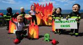 Sejumlah orang bertopeng para pemimpin dunia menggelar protes terkait kebakaran hutan Amazon jelang KTT G-7 di Biarritz, Prancis, Jumat (23/8/2019). (AP Photo/Peter Dejong)