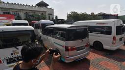 Seorang pewarta mengambil gambar mobil travel gelap yang disita di halaman Polres Metro Kabupaten Bekasi, Jawa Barat, Senin (10/5/2021). Satlantas Polres Metro Bekasi mengamankan 32 travel gelap yang masih beroperasi saat larangan mudik dari tanggal 6-17 Mei 2021. (Liputan6.com/Herman Zakharia)