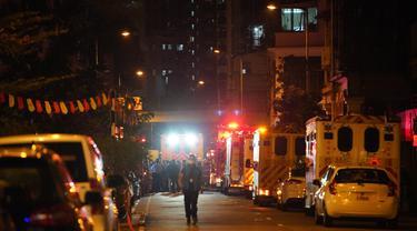 Petugas pemadam kebakaran dan polisi menyelidiki lokasi kebakaran di Hong Kong, China selatan (15/11/2020). Sebanyak tujuh orang tewas dan lebih dari 10 lainnya terluka setelah kebakaran melalap sebuah gedung apartemen di Hong Kong pada Minggu (15/11) malam, menurut kepolisian. (Xinhua/Lui Siu Wai)