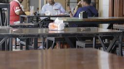 Pengunjung duduk di sebuah restoran di Bireuen, Aceh, Rabu (5/9). Selain larangan duduk bersama nonmuhrim, Pemerintah Kabupaten Bireuen juga mengeluarkan surat edaran pramusaji perempuan dilarang bekerja di atas pukul 21.00 WIB. (AFP PHOTO/AMANDA JUFRIAN)
