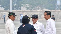 Presiden Joko Widodo berbincang dengan Menkopolhukam Wiranto, Menteri LHK Siti Nurbaya dan Seskab Pramono Anung saat meninjau kesiapan operasional pesawat penyemai yang akan membuat hujan buatan di Lanud Roesmin Nurjadin, Kota Pekanbaru, Selasa (17/9/2019). (Liputan6.com/HO/Biro Pers Setpres)