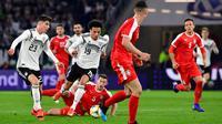 Gelandang Jerman, Leroy Sane, berusaha melewati pemain Serbia pada laga persahabatan di Stadion Volkswagen, Rabu, (20/3). Jerman ditahan imbang 1-1 oleh Serbia. (AFP/Tobias Schwarz)