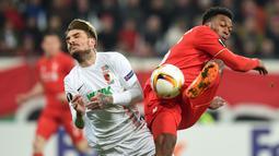 Duel antara pemain Augsburg, Konstantinos Stafylidis (kiri), dengan pemain Liverpool, Daniel Sturridge, pada laga leg pertama 32 besar Liga Europa, di WWK Arena, Augsburg, Jerman, Jumat (19/2/2016) dini hari WIB. (AFP/Christof Stache)