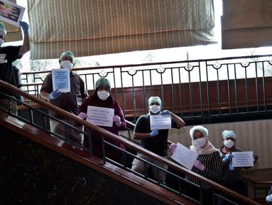 Dokter dan tenaga medis membawa tulisan berisi pesan dan tulisan untuk melawan virus corona saat sesi foto di posko tenaga medis Covid-19, Jakarta, Kamis (2/4/2020). Aksi ini mengharapkan masyarakat berdiam diri di rumah, untuk ikut bergerak memutus mata rantai covid-19. (Liputan6.com/Johan Tallo)