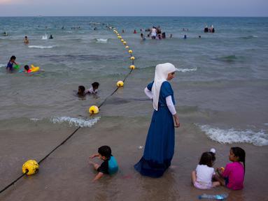 Pemandangan saat warga Palestina menghabiskan libur Idul Fitri di pantai Tel Aviv, Israel, Sabtu (16/6). Pemerintah Israel mengizinkan warga Palestina untuk berwisata di sepanjang garis pantai Mediterania selama Idul Fitri. (AP Photo/Oded Balilty)