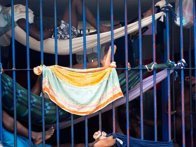 Para narapidana mengunakan tempat tidur gantung beristirahat di dalam selnya di Lapas Nasional di pusat kota Port-au-Prince, Haiti, (13/2). Sebagian narapidana, belum menjalani sidang putusan atas kejahatan yang dilakukannya. (AP Photo/Dieu Nalio Chery)