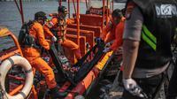 Petugas Basarnas menurunkan kantung jenazah dan serpihan pesawat Lion Air JT 610 di Posko Evakuasi, Tanjung Priok, Jakarta, Senin (29/10). Pesawat Lion Air JT 610 dipastikan jatuh di laut utara Karawang. (Liputan6.com/Faizal Fanani)
