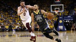 Pebasket Golden State Warriors, Stephen Curry, berusaha melewati pebasket Cleveland Cavaliers, Kevin Love, pada final NBA di Oracle Arena, Oakland, Minggu (3/6/2018). Warriors menang 122-103 atas Cavaliers. (AFP/Ezra Shaw)