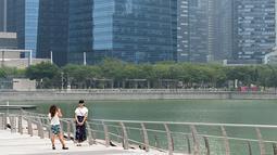 Seorang wanita saat difoto dengan rekannya di sepanjang kawasan pejalan kaki di Marina Bay di Singapura (13/9/2019). Kebakaran hutan yang terjadi di Indonesia membuat kekhawatiran tentang dampak meningkatnya wabah api di seluruh dunia pada pemanasan global. (AFP Photo/Roslan Rahman)
