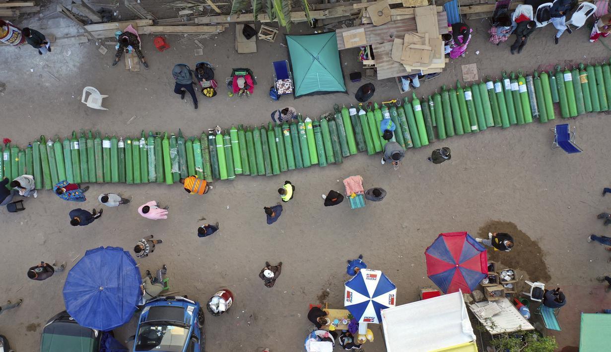 Lusinan tabung oksigen kosong tergeletak di jalan ketika orang-orang menunggu toko buka untuk mengisi tabung mereka di Villa El Salvador, Lima, Peru, Selasa (6/4/2021). Warga Peru terus berjuang mendapatkan oksigen medis untuk merawat pasien COVID-19. (AP Photo/Rodrigo Abd)