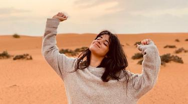 Camila Cabello tampak berpose hanya menggunakan sweater di sebuah padang pasir di negeri Arab. Gadis berusia 22 tahun ini tampak sangat bahagia dengan senyum yang mengembang dan kedua tangan diangkat ke atas. (Liputan6.com/IG/@camila_cabello)