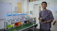 Mahasiswa Politeknik Caltex Riau memperlihatkan minuman hasil adukan mesin pencampur otomatis ciptaannya. (Liputan6.com/M Syukur)