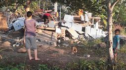 Warga memeriksa reruntuhan rumah yang rusak akibat gempa di Lombok, NTB, Minggu (29/7). Data sementara mencatat, gempa bumi tektonik 6.4 SR itu mengakibatkan 10 orang meninggal dunia dan puluhan rumah rusak. (HO/NTB DISASTER MITIGATION AGENCY/AFP)