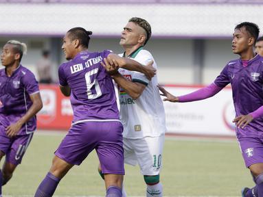 Striker PSS Sleman, Cristian Gonzales, dijaga ketat pemain Persita Tangerang pada laga Liga 2 di Stadion Benteng Taruna, Tangerang, Jumat (26/10/2018). Kedua tim bermain imbang 1-1. (Bola.com/M Iqbal Ichsan)