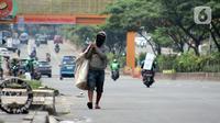 Pemulung berjalan di Jalan Margonda Raya, Depok, Kamis (16/4/2020). Pandemi COVID-19 memberikan dampak yang sangat besar bagi sosial dan ekonomi Indonesia. Bahkan yang paling dikhawatirkan bertambahnya angka kemiskinan dan pengangguran. (Liputan6.com/Helmi Fithriansyah)