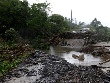 Jembatan penghubung ambruk diterjang gelombang Tsunami Selat Sunda di jalur alternatif Sumur, Banten, Senin (24/12). Sejumlah kendaraan terpaksa melintasi pantai karena jembatan tidak bisa dilewati. (Liputan6.com/Angga Yuniar)