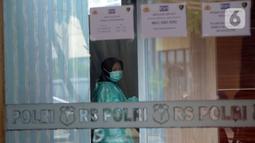 Seorang wanita yang mengenakan masker terliat di Posko Ante Mortem-DVI RS Polri Jakarta, Selasa (12/1/2021). Hingga saat ini, tim DVI masih mengumpulkan sampel DNA penumpang pesawat Sriwijaya Air SJ 182 yang jatuh di perairan Kepualauan Seribu. (merdeka.com/Imam Buhori)