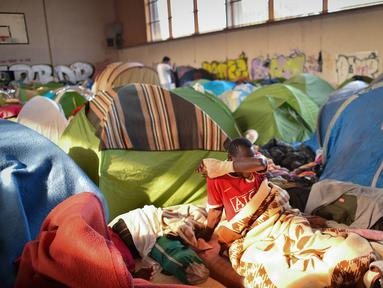 Seorang pria terbangun di gimnasium yang ditempati migran di lycee Jeanne-Bernard di Saint-Herblain, Nantes, Prancis (28/3). Sebuah keputusan pengadilan 28 Maret 2019, menyusul  permintaan  keuskupan, pemilik situs, untuk mengusir para migran yang menempati gymnasium.  (AFP Photo/Loic Venance)