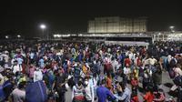 Ratusan buruh migran menunggu di terminal bus untuk berangkat ke desa mereka, New Delhi, India, Senin (19/4/2021). Pihak berwenang mengatakan pada hari Senin bahwa rumah sakit telah didorong hingga batasnya. (AP Photo)