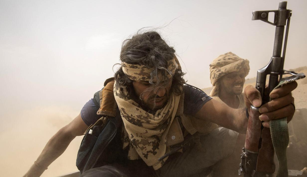 Pejuang Yaman yang didukung oleh koalisi pimpinan Arab Saudi naik di belakang kendaraan lapis baja saat mereka meninggalkan garis depan Marib, Yaman, 19 Juni 2021. (AP Photo/Nariman El-Mofty)