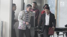 Gubernur Jambi Zumi Zola memasuki Gedung KPK untuk menjalani pemeriksaan, Jakarta, Kamis (15/2). Didampingi dua orang pria, Zumi Zola tampak santai dan sesekali tersenyum pada awak media. (Liputan6.com/Herman Zakharia)