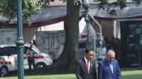 Presiden Joko Widodo (Jokowi) berjalan bersama PM Malaysia, Mahathir Mohamad usai menaman pohon di halaman belakang Istana Bogor, Jumat (29/6). Sebelum kegiatan menanam pohon, PM Malaysia disambut dengan upacara kenegaraan. (Liputan6.com/Angga Yuniar)