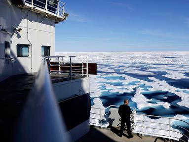 Kapten penjaga pantai Kanada Victor Gronmyr melihat es yang menutupi Selat Victoria dari atas kapal pemecah es Finlandia MSV Nordica saat melintasi Northwest Passage melalui Kepulauan Arktik Kanada (22/7). (AP Photo/David Goldman)
