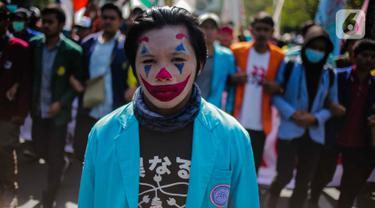 Massa mahasiswa dari BEM Seluruh Indonesia (SI) memakai riasan tokoh Joker dalam unjuk rasa di kawasan Patung Kuda, Jakarta, Senin (21/10/2019). Salah satu tuntutannya adalah meminta Presiden Jokowi menerbitkan Perppu untuk UU KPK yang direvisi. (Liputan6.com/Faizal Fanani)