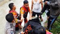 Polisi dan Basarnas Pekanbaru mengevakuasi korban terseret banjir.(Www.sulawesita.com)