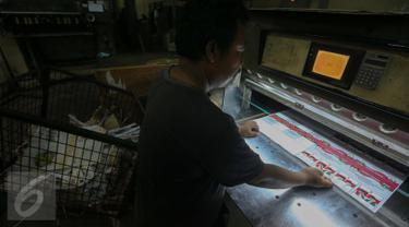 Pekerja menyelesaikan pencetakan surat suara Pemilihan Kepala Daerah di Provinsi Banten di Kawasan Industri Pulo Gadung, Jakarta, Rabu (11/1). Sebanyak 7.900.000 lembar surat suara dicetak oleh PT Dian Rakyat. (Liputan6.com/Faizal Fanani)